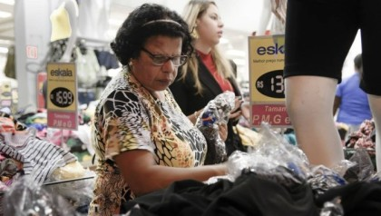 Consumidora olha produto em loja de centro comercial